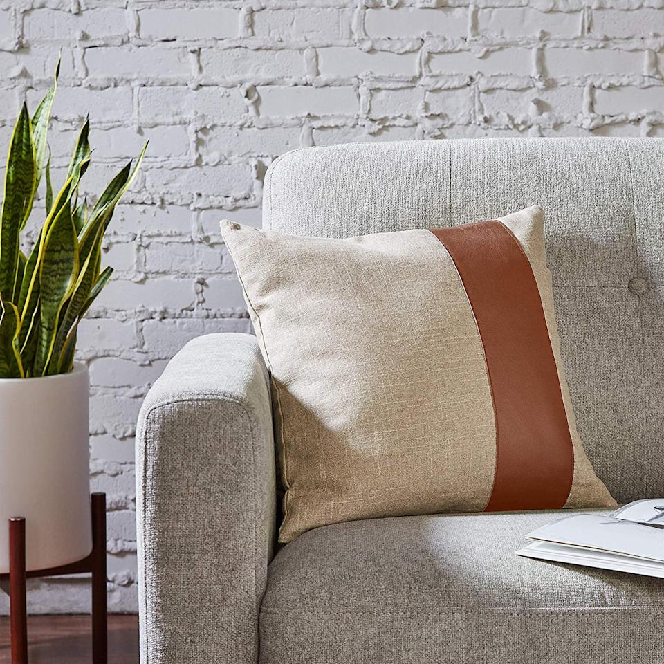 """<p>Going for a more minimal look? You can't go wrong with this <product href=""""https://www.amazon.com/Rivet-Industrial-Throw-Pillow-Cognac/dp/B07JLSP8JF/ref=sr_1_10?crid=55IUR6JN5D9M&amp;keywords=rivet+throw+pillows&amp;qid=1572457686&amp;sprefix=rivet+throw+%2Caps%2C219&amp;sr=8-10"""" target=""""_blank"""" class=""""ga-track"""" data-ga-category=""""Related"""" data-ga-label=""""https://www.amazon.com/Rivet-Industrial-Throw-Pillow-Cognac/dp/B07JLSP8JF/ref=sr_1_10?crid=55IUR6JN5D9M&amp;keywords=rivet+throw+pillows&amp;qid=1572457686&amp;sprefix=rivet+throw+%2Caps%2C219&amp;sr=8-10"""" data-ga-action=""""In-Line Links"""">Rivet Industrial Throw Pillow</product> ($46).</p>"""