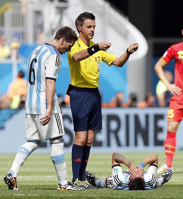 Argentina's Lucas Biglia (6) checks on his teammate Angel di Maria while referee Nicola Rizzoli from Italy calls for a stretcher during the World Cup quarterfinal soccer match between Argentina and Belgium at the Estadio Nacional in Brasilia, Brazil, Saturday, July 5, 2014. (AP Photo/Victor R. Caivano)