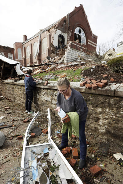 Debbie Jones takes a piece of a broken window from East End United Methodist Church after it was heavily damaged by a storm Tuesday, March 3, 2020, in Nashville, Tenn. Jones attended the church when she was a child.  Tornadoes ripped across Tennessee early Tuesday, shredding buildings and killing multiple people.  (AP Photo/Mark Humphrey)