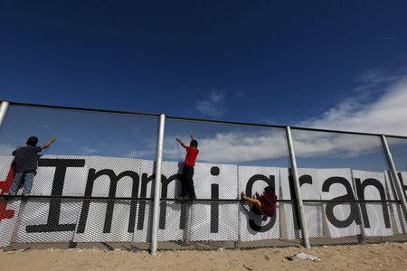 Children climb up the border fence between Ciudad Juarez and El Paso, United States, during a bi-national Mass in support of migrants in Ciudad Juarez, Mexico, February 15, 2016. REUTERS/Jose Luis Gonzalez