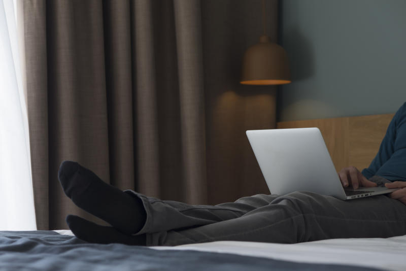 Young man lying on bed using laptop, partial view