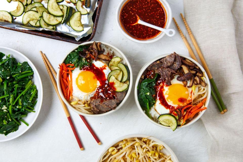 """<p>The veggie, meat, and egg in this Bibimbap cook in different sections of the sheet pan. Toss with steamy rice and gochujang sauce for a gorgeous variety of flavor, color, and texture.</p><p>Get the recipe from <a href=""""https://www.delish.com/cooking/recipe-ideas/a36007712/sheet-pan-bibimbap-recipe/"""" rel=""""nofollow noopener"""" target=""""_blank"""" data-ylk=""""slk:Delish"""" class=""""link rapid-noclick-resp"""">Delish</a>.</p>"""