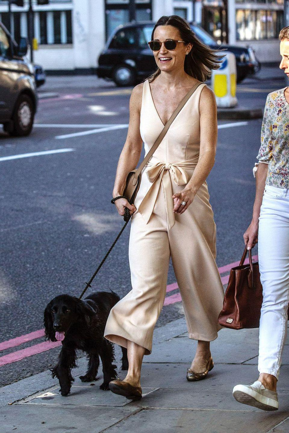 <p>In a nude silk jumpsuit and ballet flats while out walking her dog.</p>