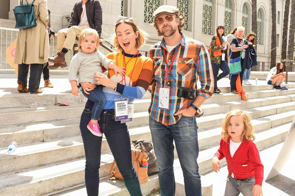 """Olivia Wilde with her crew — partner Jason Sudeikis and kids Daisy, almost 2, and Otis, 4 — at March for Our Lives Los Angeles in March 2018. Sudeikis appears in her directorial debut, and she says working with him was """"great. I mean, directing a good actor is like driving a Ferrari. They're very well-tuned, so you make tiny adjustments and they can do anything."""" (Photo: Presley Ann/WireImage)"""
