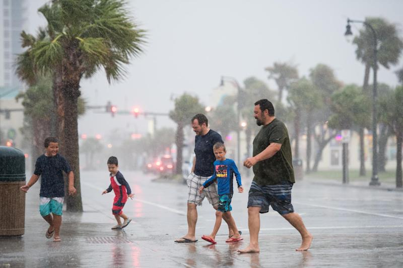 People walk across Ocean Boulevard in Myrtle Beach, South Carolina as Hurricane Isaias continued to move north along the eastern seaboard: Getty Images