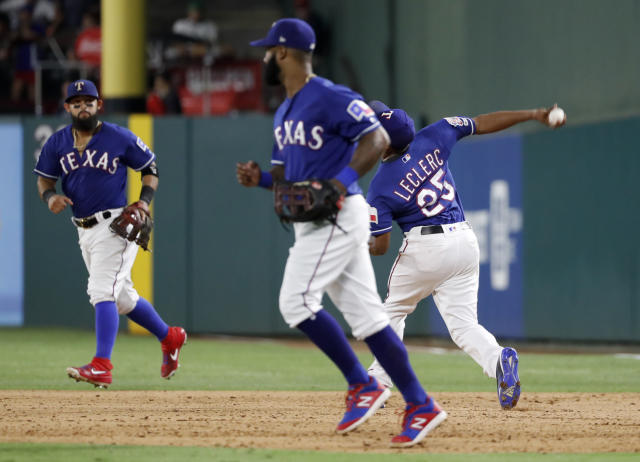 Texas Rangers' Rougned Odor, rear, and Danny Santana, front, jog to join the team in celebration as relief pitcher Jose Leclerc throws a ball following the team's 5-4 win against the Detroit Tigers in a baseball game in Arlington, Texas, Friday, Aug. 2, 2019. Leclerc threw the ball after covering first for the final out of the game. (AP Photo/Tony Gutierrez)