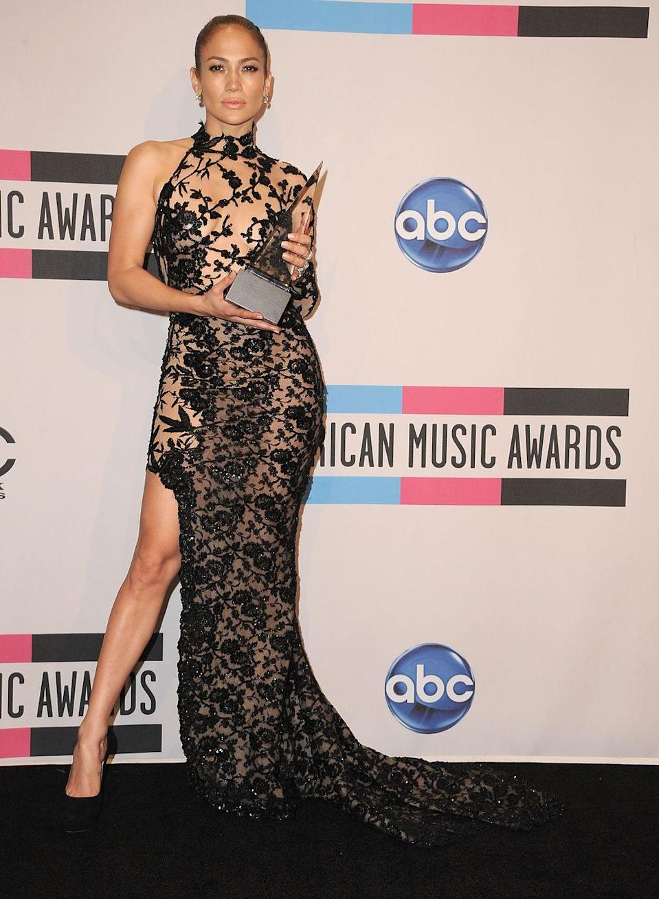 <p>J.Lo accepts her win for Favorite Latin Artist at the VMAs in this stunning one-shoulder sequined dress with a halter neckline and asymmetrical hem. I stan a dramatic leg pose! </p>