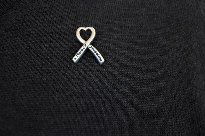 In this Saturday, March 23, 2019 photo, a pin on Rick Townsend's sweater memorializes his daughter, Lauren, who was killed in the April 20, 1999, mass shooting at Columbine High School in suburban Denver. Several survivors and family members of the victims gathered at the school's library to speak to the media Saturday. (AP Photo/Thomas Peipert)