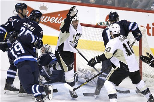 Pittsburgh Penguins' Craig Adams, center, celebrates his goal with teammate Tanner Glass (10) on Winnipeg Jets goaltender Ondrej Pavelec, rear, during the first period of an NHL hockey game in Winnipeg, Manitoba, on Friday, Feb. 15, 2013. (AP Photo/The Canadian Press, John Woods)