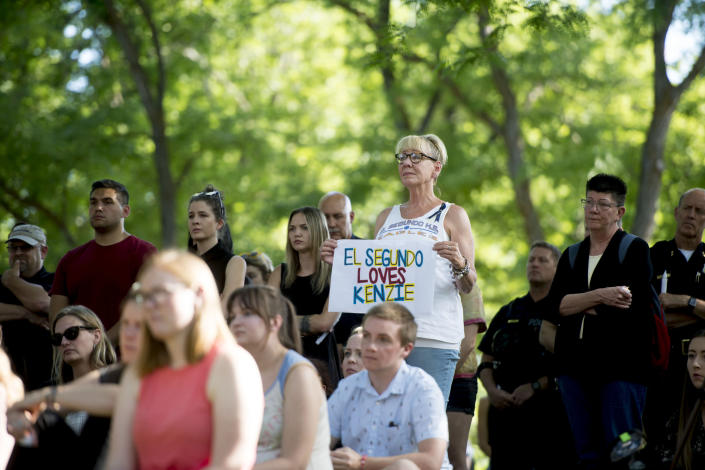 Denise Dial, a longtime friend of the Lueck family, holds a sign in remembrance of Mackenzie Lueck during a vigil for Mackenzie Lueck at the university in Salt Lake City on Monday, July 1, 2019. Friends and mourners gathered Monday night to remember Lueck, a Utah college student who was missing for nearly two weeks before police arrested a man accused of killing her and burying her charred remains in his backyard. (Jeremy Harmon/The Salt Lake Tribune via AP)