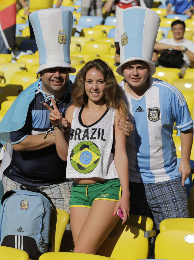 Argentine fans pose next to a Brazilian fan, center, before the start of the World Cup final soccer match between Germany and Argentina at the Maracana Stadium in Rio de Janeiro, Brazil, Sunday, July 13, 2014. (AP Photo/Victor R. Caivano)