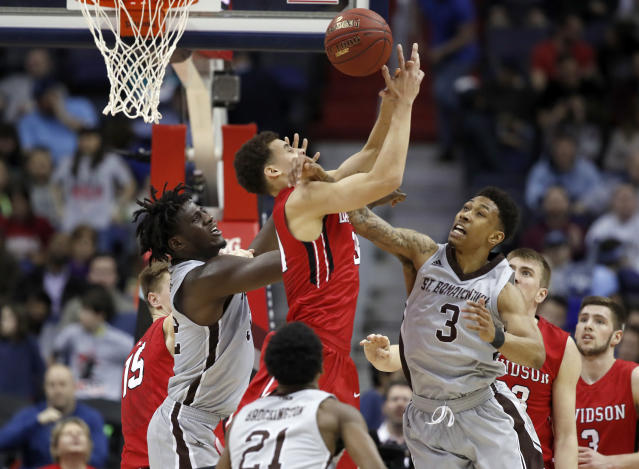 St. Bonaventure center Amadi Ikpeze (32), Davidson guard Kellan Grady (31) and St. Bonaventure guard Jaylen Adams (3) go for the rebound during the first half of an NCAA college basketball game in the semifinals of the Atlantic 10 Conference tournament, Saturday, March 10, 2018, in Washington. (AP Photo/Alex Brandon)