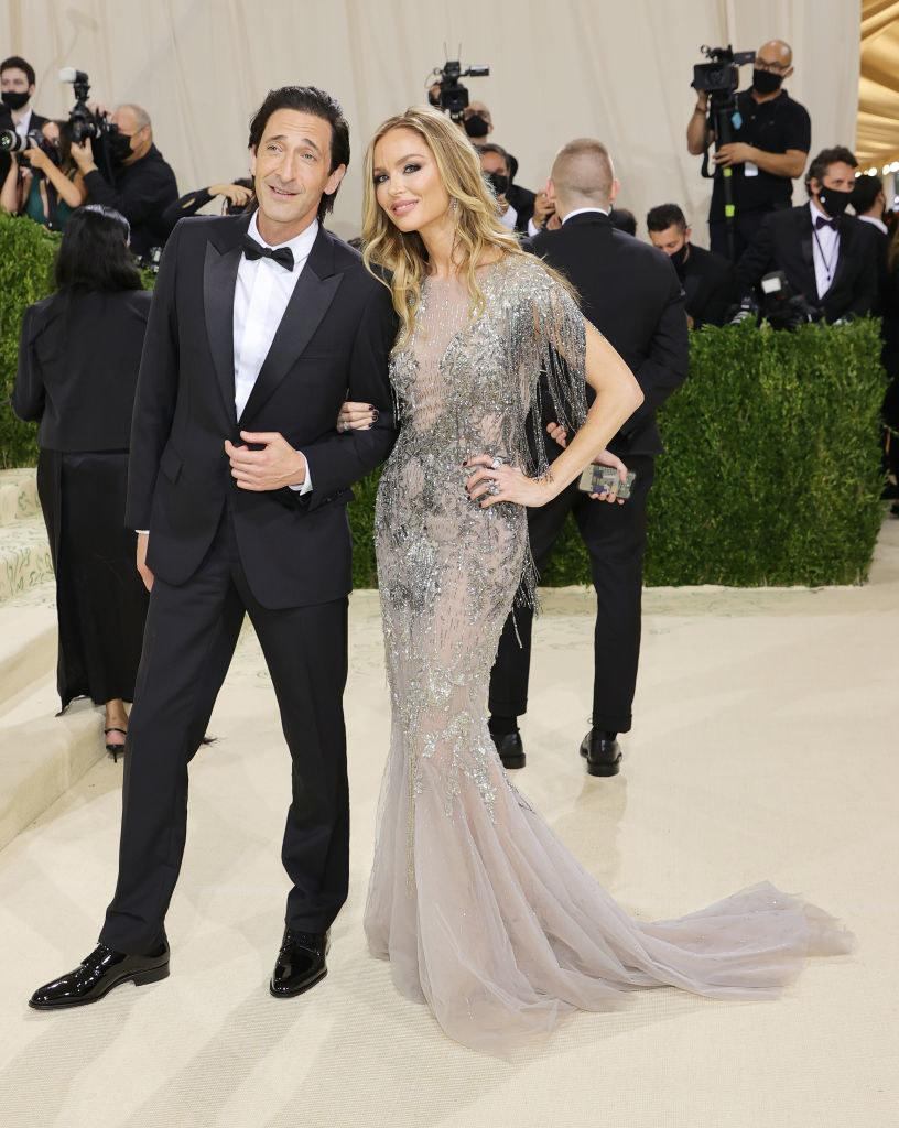 Adrien Brody wears a dark suit and Georgina Chapman wears a floor length gown with sparkles on the bodice and a long train