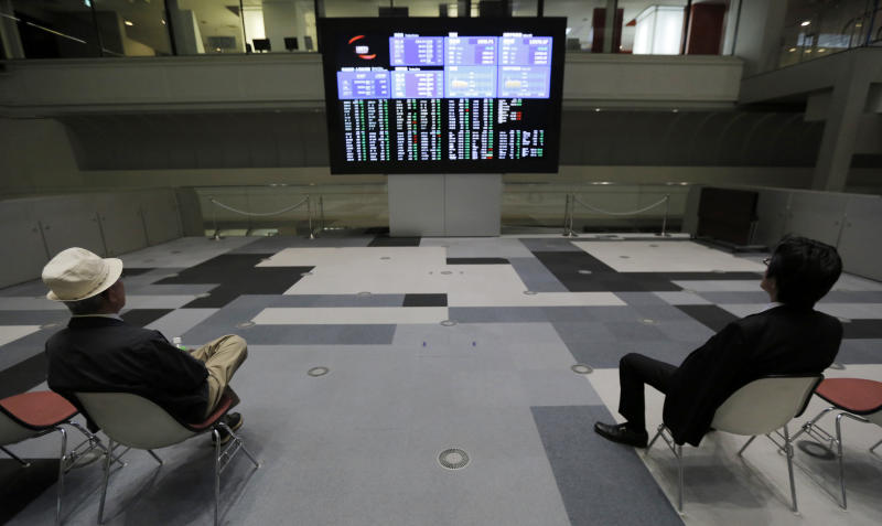 Men look at an electronic stock board at the Tokyo Stock Exchange in Tokyo, Friday, June 7, 2013. Asian stock markets fell Friday, ignoring a rebound on Wall Street, as investors stayed on the sidelines ahead of a key U.S. jobs report later in the day. (AP Photo/Itsuo Inouye)