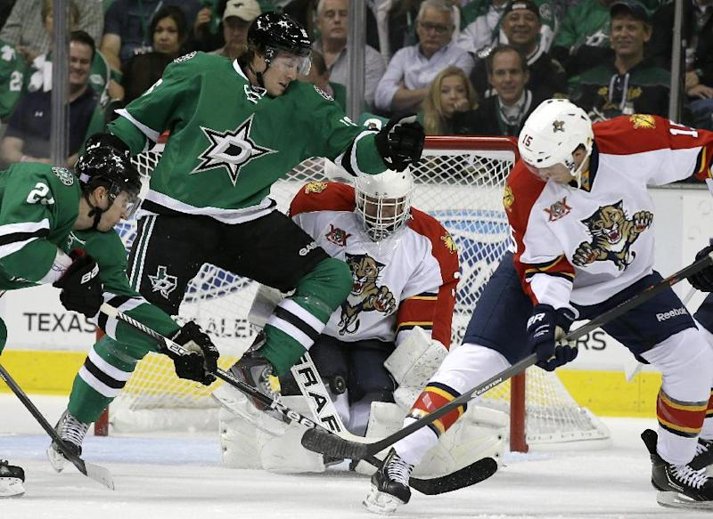 Dallas Stars' Antoine Roussel, left, of France, and center Ryan Garbutt, second from left, pressure the net as Florida Panthers goalie Tim Thomas blocks a shot with his legs as Panthers center Drew Shore (15) watches in the first period of an NHL hockey game, Thursday, Oct. 3, 2013, in Dallas. (AP Photo/Tony Gutierrez)
