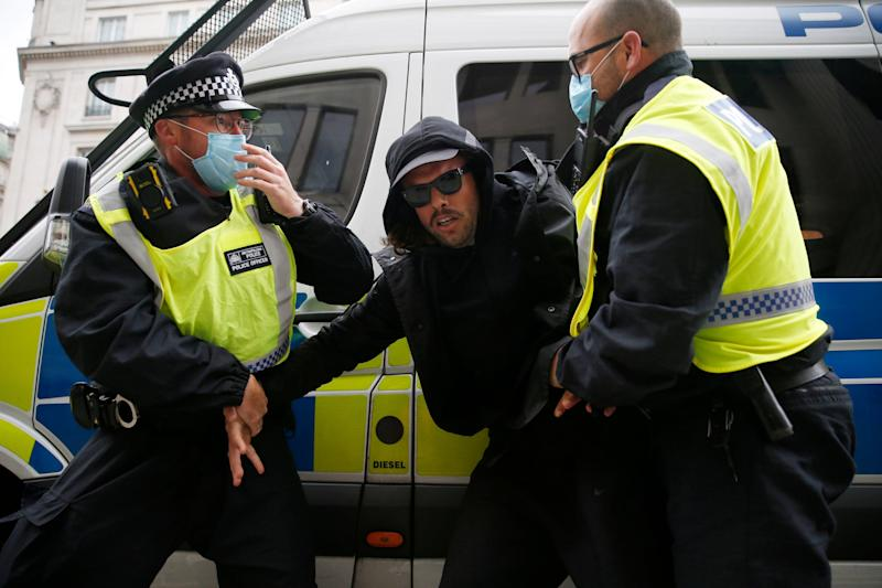 A man is arrested by police officers during a