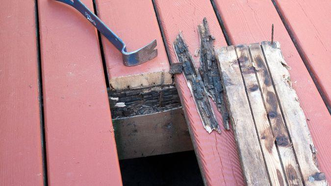 Old cedar damaged by wet rot on deck removed and prepared for new decking.