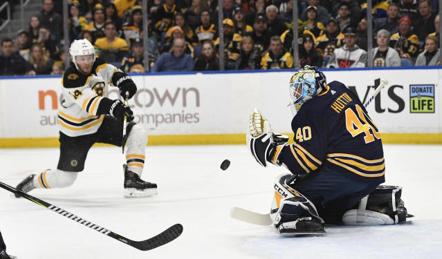 Buffalo Sabres goalie Carter Hutton (40) deflects a shot by Boston Bruins right wing Chris Wagner during the first period of an NHL hockey game in Buffalo, N.Y., Saturday, Dec. 29, 2018. (AP Photo/Adrian Kraus)