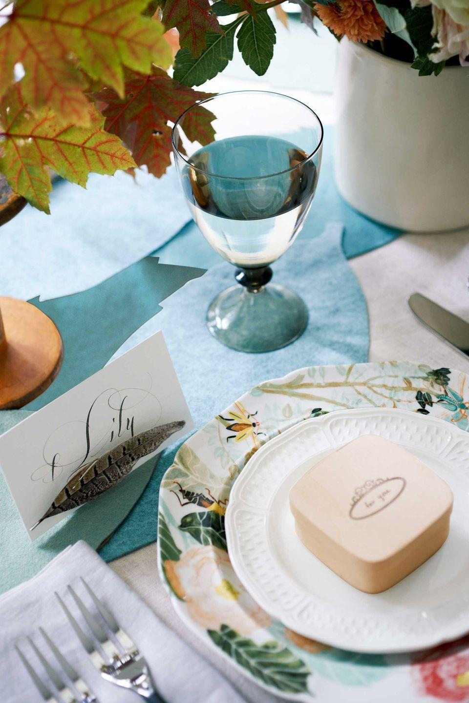 """<p>Let nature take its course with a DIY leaf runner. Crafted from lush blue and green felt, this table topper perks up plain linens and provides a padded path for hot plates. Download our <a href=""""http://clv.h-cdn.co/assets/cm/15/24/5578b8d213937_-_leaf-table-runner.pdf"""" rel=""""nofollow noopener"""" target=""""_blank"""" data-ylk=""""slk:leaf template"""" class=""""link rapid-noclick-resp"""">leaf template</a> and use it to cut the shapes out of felt. Create enough leaves to traverse your table, then hand-stitch the edges together in a whimsical, overlapping design. </p><p>A feather placecard lends a fine finish. More than just a way to denote seating arrangements, this pretty plumage doubles as wearable art—thanks to a bar pin hot-glued to the back. Make the quill stand upright by hot-gluing a magnet to the side of a cork, then sliding the placecard between the feather pin and cork magnet. As for the gorgeous handwriting, we splurged on professional calligraphy. </p><p><a class=""""link rapid-noclick-resp"""" href=""""https://www.amazon.com/Blue-Tones-Multi-Pack-Sheets-Merino/dp/B07NLHR3YM/ref=sr_1_24?tag=syn-yahoo-20&ascsubtag=%5Bartid%7C10050.g.1371%5Bsrc%7Cyahoo-us"""" rel=""""nofollow noopener"""" target=""""_blank"""" data-ylk=""""slk:SHOP KRAFT BLUE FELT"""">SHOP KRAFT BLUE FELT</a></p>"""