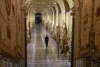 "Gianni Crea, the Vatican Museums chief ""Clavigero"" key- keeper, walks down an aisle on his way to open the museum's rooms and sections, the Vatican, Monday, Feb. 1, 2021. Crea is the ""clavigero"" of the Vatican Museums, the chief key-keeper whose job begins each morning at 5 a.m., opening the doors and turning on the lights through 7 kilometers of one of the world's greatest collections of art and antiquities. The Associated Press followed Crea on his rounds the first day the museum reopened to the public, joining him in the underground ""bunker"" where the 2,797 keys to the Vatican treasures are kept in wall safes overnight. (AP Photo/Andrew Medichini)"