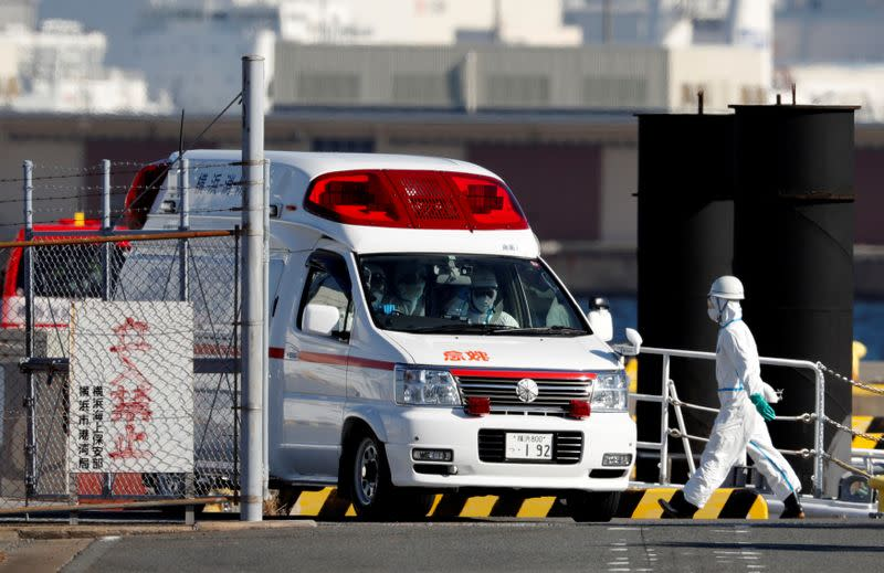Ambulance workers in protective gear drive an ambulance which is believed to carry a person who was transferred from cruise ship Diamond Princess after ten people tested positive for coronavirus, at a maritime police's base in Yokohama