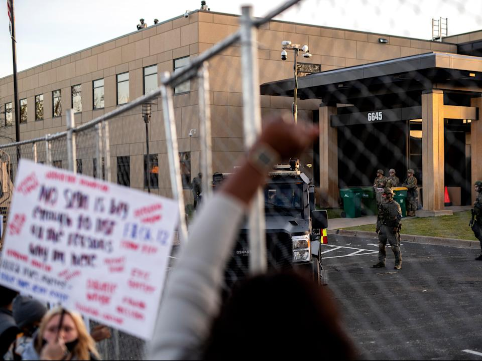 <p>Police officers stand guard as demonstrators gather during a protest outside the Brooklyn Center police station on 16 April, 2021 in Brooklyn Center, Minnesota</p> (Getty Images)