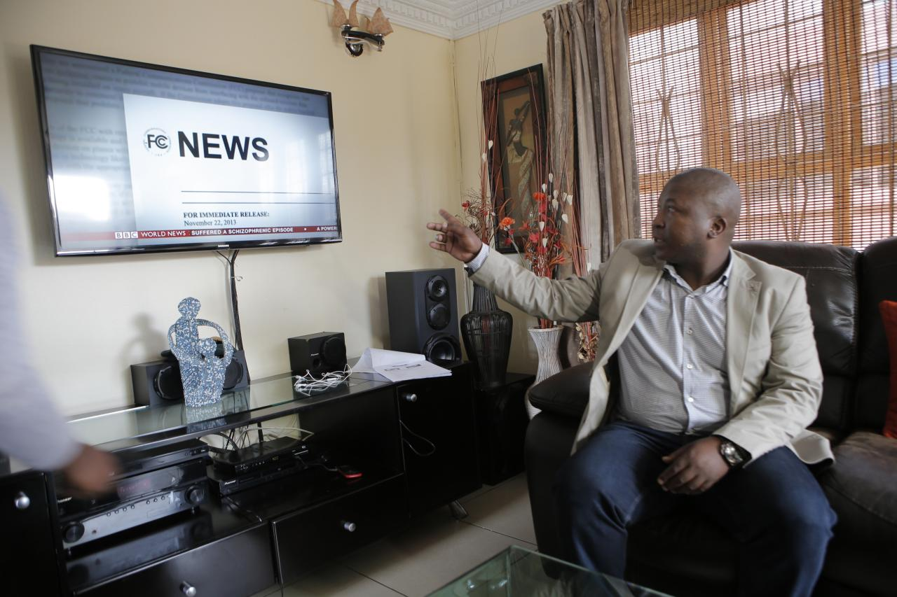 Thamsanqa Jantjie looks around at a television at his home during an interview with the Associated Press in Johannesburg, South Africa,Thursday, Dec. 12, 2013. Jantjie, the man accused of faking sign interpretation next to world leaders at Nelson Mandela's memorial, told a local newspaper that he was hallucinating and hearing voices. (AP Photo/Tsvangirayi Mukwazhi)