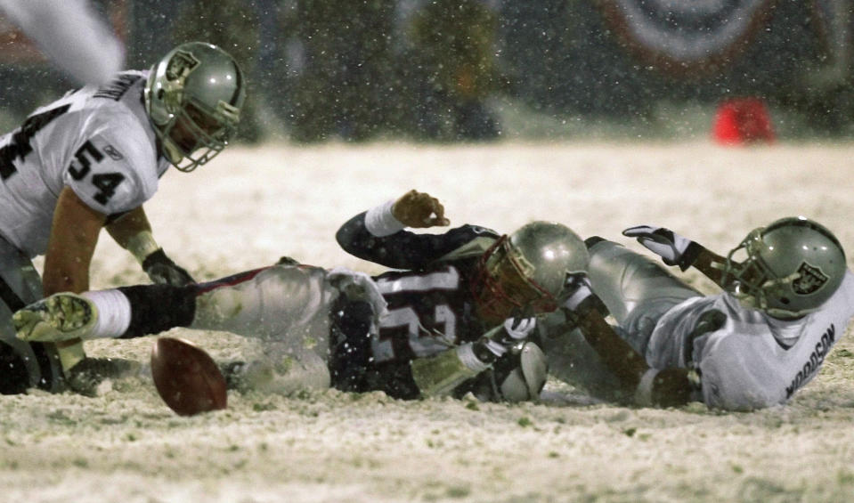New England Patriots quarterback Tom Brady (12) loses the ball after being brought down by Oakland Raiders' Charles Woodson in the famous Tuck Rule game . (AP Photo/Elise Amendola, File)