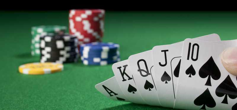 Poker hand showing a royal flush on a poker table with chips in background.