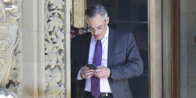 Conservative MP Tony Clement checks his phone on Parliament Hill in Ottawa on May 11, 2016.