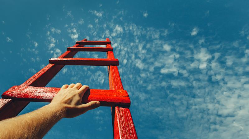 A hand holding the bottom rung of a red ladder set against a clear, blue sky.