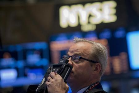 A trader looks up at a screen on the floor of the New York Stock Exchange May 1, 2014. REUTERS/Brendan McDermid
