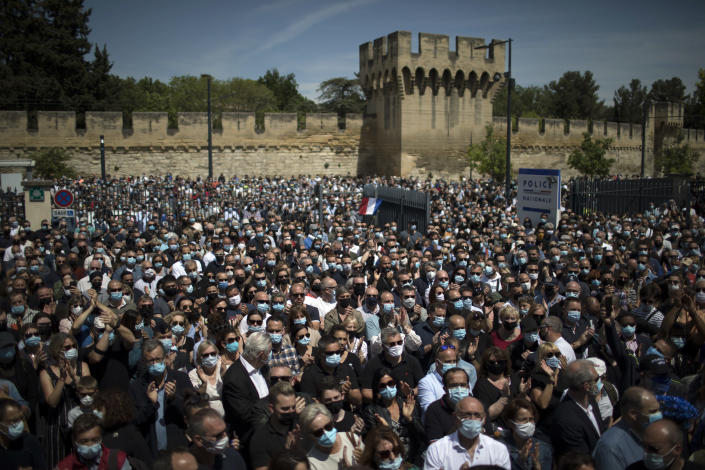 Police officers and civilians gather at a police station in Avignon, southern France, Sunday, May 9, 2021. Police officers and civilians gathered to commemorate the death of a police officer who was killed Wednesday at a known drug-dealing site in the southern France city of Avignon. (AP Photo/Daniel Cole)