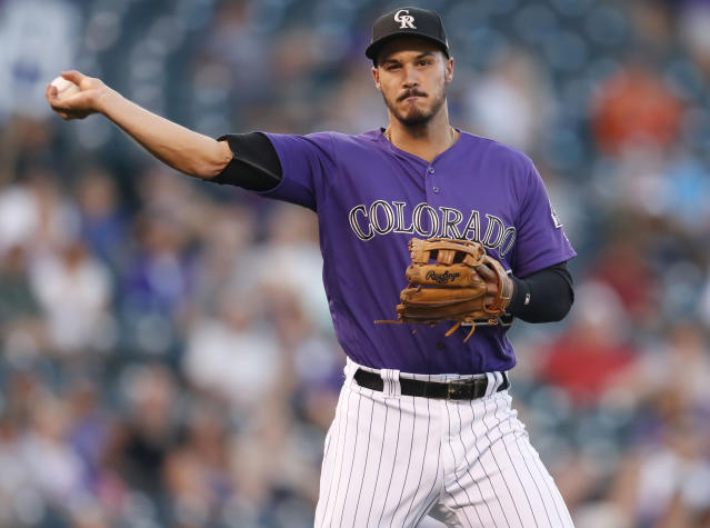 FILE - In this Sept. 12, 2018, file photo, Colorado Rockies third baseman Nolan Arenado throws to first base to put out Arizona Diamondbacks' A.J. Pollock in the first inning of a baseball game in Denver. AL MVP Mookie Betts, NL Cy Young Award winner Jacob deGrom and major league home run champion Khris Davis reached high-priced one-year deals to avoid salary arbitration, while Arenado and pitchers Gerrit Cole, Luis Severino and Aaron Nola failed to reach agreements and for now appeared headed to hearings. (AP Photo/David Zalubowski, File)