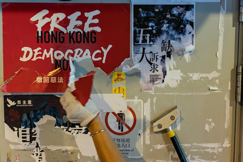 A pro-China supporter pulls down walls of pro-democracy posters and Post-it notes: Getty Images