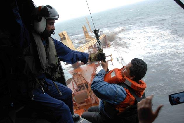A crew member is winched onto an Indian Navy rescue helicopter from the sinking merchant ship MV Rak.