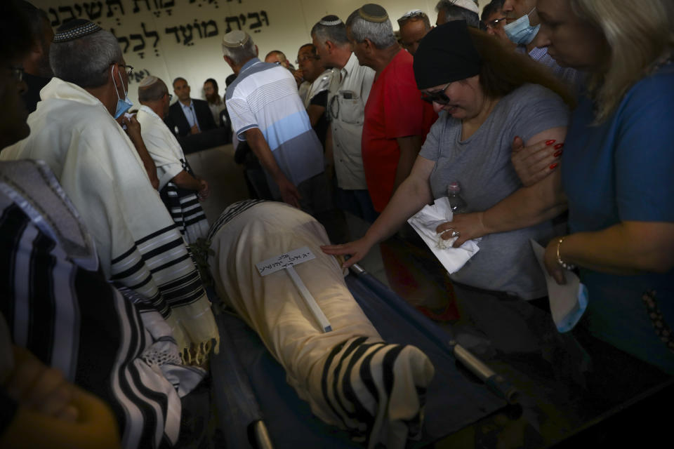 Mourners attend the funeral of Yigal Yehoshua, 56, at a cemetery in Hadid, central Israel, Tuesday, May 18, 2021. Yehoshua died of wounds sustained in when his car was pelted with rocks during Israeli Arab riots in the Israeli city of Lod on May 11. (AP Photo/Oded Balilty)