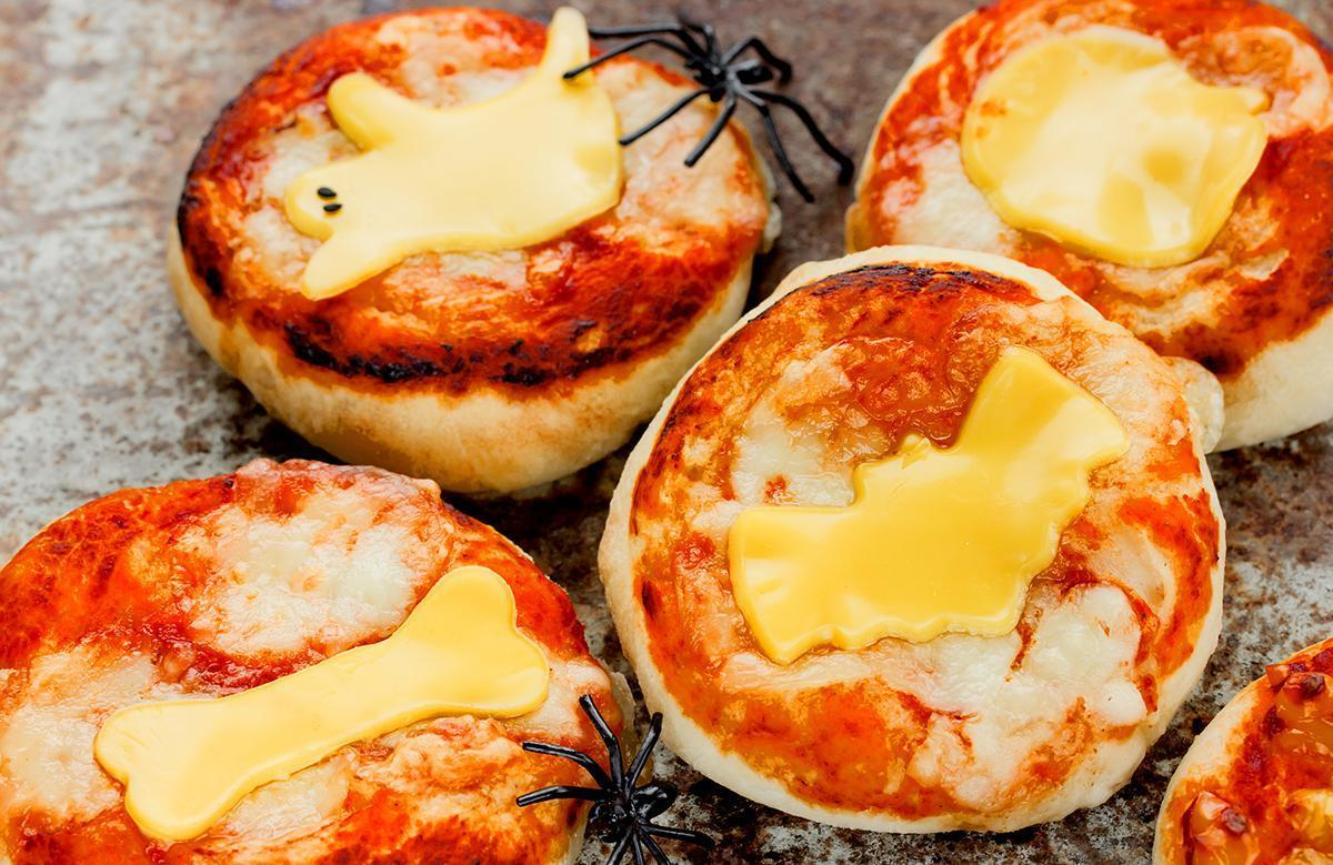 "<p>Pizza bagels are a snack we all loved as children and it's easy to make into a Halloween treat. After using a <a href=""https://www.thedailymeal.com/pizza-bagel-recipe?referrer=yahoo&category=beauty_food&include_utm=1&utm_medium=referral&utm_source=yahoo&utm_campaign=feed"">pizza bagel recipe</a> to create a perfectly baked piece of dough covered in marinara sauce, cut a slice of cheese of your choice into the shape of a friendly ghoul. If you're a fan of olives, cut a few into little pieces for eyes, and ta-da! You've got pizza perfect for a Halloween shindig.</p>"