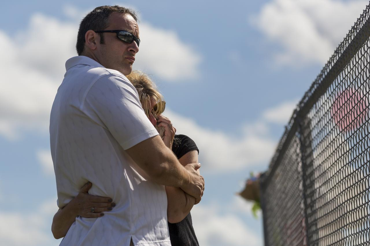 Mourners hug near a makeshift memorial created by community members outside of Marjory Stoneman Douglas High School in Parkland, Fla., on Sunday, Feb. 18, 2018. A gunman entered the school last Wednesday and killed 17 students and teachers. (Matias J. Ocner/Miami Herald via AP)