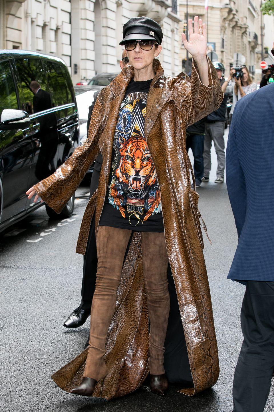 <p>Oh this old thing? Celine went out on a hot summer day in this floor-length snake-embossed Balmain coat, brown thigh-high suede boots, and a black leather cap. <br></p>