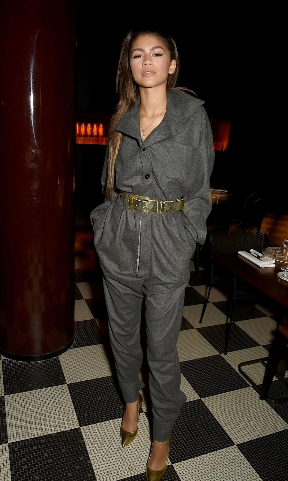<p>Attending the <i>Hunger Magazine</i> & Vivienne Westwood Paris Fashion Week Event, Zendaya celebrated at Les Bains in a jumpsuit made by the outspoken British designer. She paired some bright gold stilettos and a matching belt with the gray piece for some pop. <br></p><p><i>Photo: Getty Images</i><br></p>