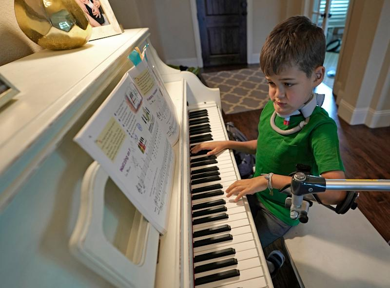 Braden Scott uses a device to support his left arm as he practices on the piano. (Photo: ASSOCIATED PRESS)