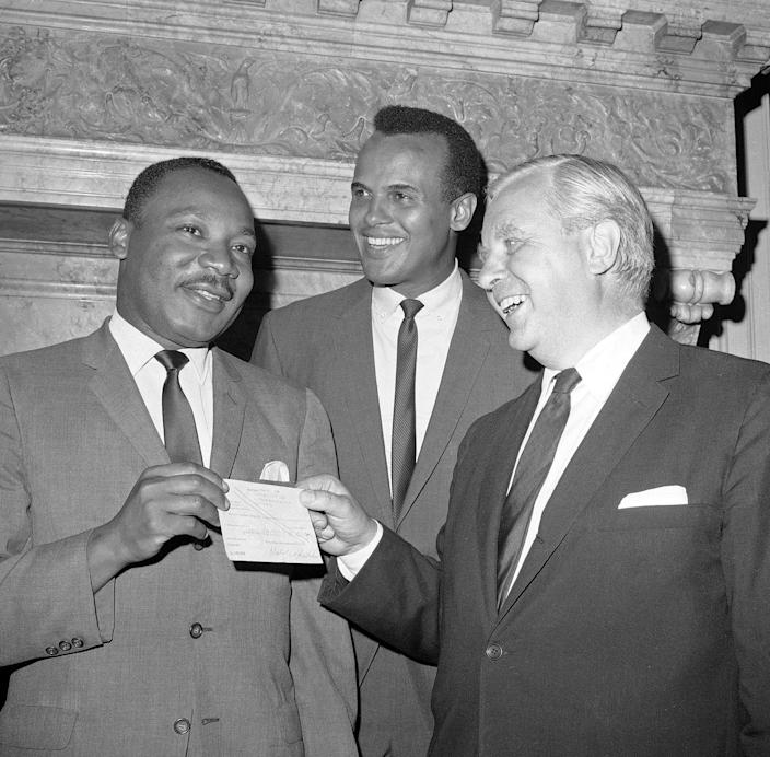<p>The Consul-General for Sweden in New York City, Tore Tallroth, right, presents a $100,000 check to Dr. Martin Luther King, left, at Sweden House in New York, July 5, 1966. Singer-actor Harry Belafonte stands at center. (AP Photo/Jacob Harris) </p>