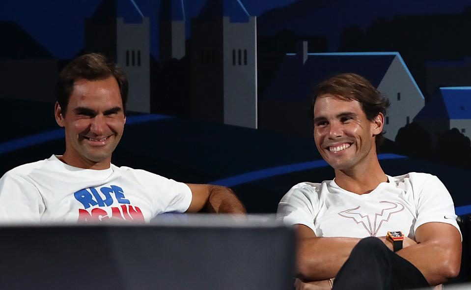 Rafael Nadal and Roger Federer laugh on the sideline of a match.