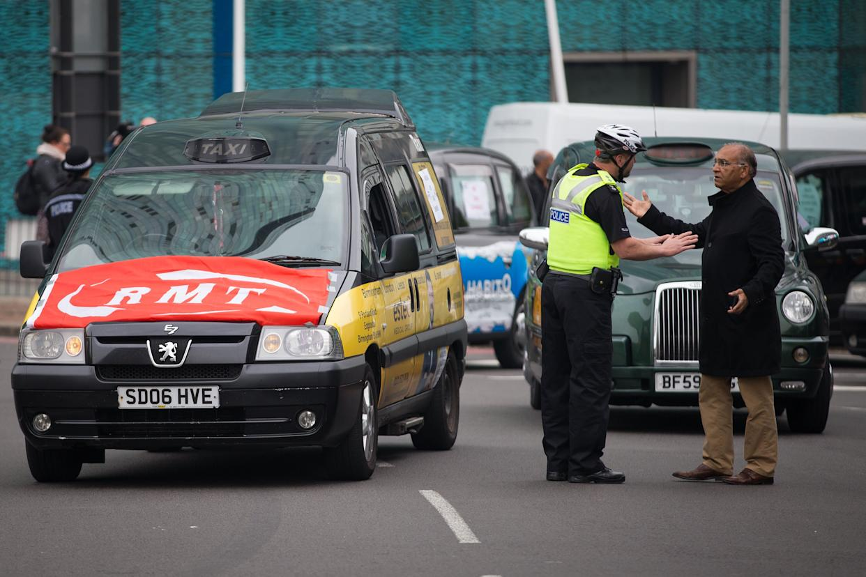 Police officers direct traffic as taxis engage in a 'go slow' protest on the Holloway Circus roundabout in Birmingham City Centre as drivers protest over the city councils plans for a new clean air zone in Birmingham.