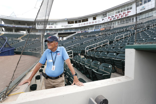 Hammond Stadium usher Ken Trammell looks out on an empty stadium, Thursday, March 12, 2020, in Fort Myers, Fla. Major League Baseball has suspended the rest of its spring training game schedule because if the coronavirus outbreak. MLB is also delaying the start of its regular season by at least two weeks. (AP Photo/Elise Amendola)