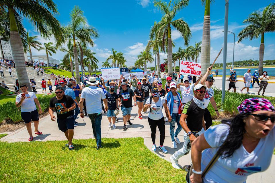 Cuban and Venezuelan protesters march outside the stadium before Monday's game.