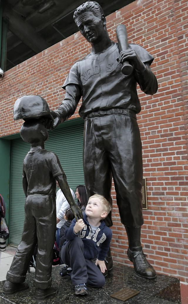 Mason Sutherland, 4, of Peabody, Mass., climbs on a statue of former Boston Red Sox baseball player Ted Williams and a child outside Fenway Park, Thursday, Oct. 31, 2013, in Boston. The Red Sox defeated the St. Louis Cardinals 6-1 in Game 6 of baseball's World Series on Wednesday to win the series. (AP Photo/Steven Senne)
