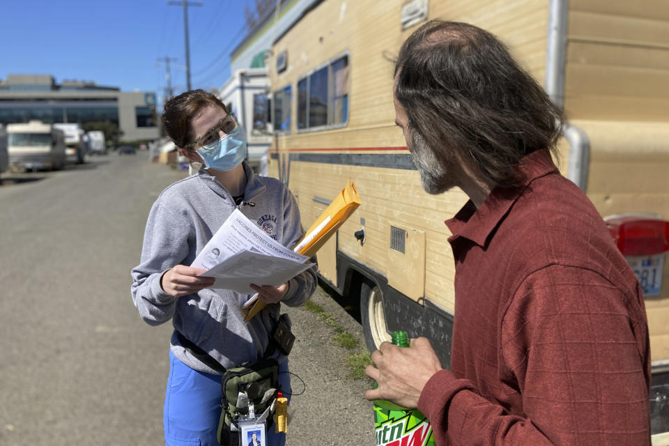 Moira Andrews, a street outreach nurse for Neighborcare Health, speaks with Shane Pisson, 48, who lives in an encampment in the Georgetown neighborhood of Seattle on Monday, April 12, 2021. Andrews spoke with Pisson about the COVID-19 vaccines and answered questions in an effort to vaccinate people experiencing homelessness. Advocates say homeless people are at greater risk of being infected and greater risk of hospitalization and death than the average person, and they should have been prioritized earlier. (AP Photo/Manuel Valdes)