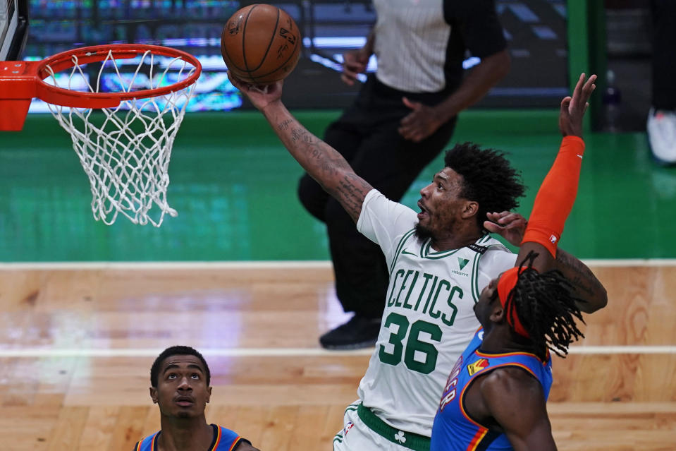 Boston Celtics guard Marcus Smart (36) drives to the basket past Oklahoma City Thunder forward Luguentz Dort, right, during the first half of an NBA basketball game, Tuesday, April 27, 2021, in Boston. (AP Photo/Charles Krupa)